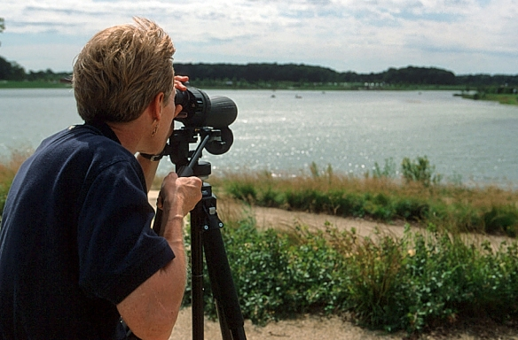 An educator searches for birds at Independence Grove. Photo © Lake County Forest Preserves.