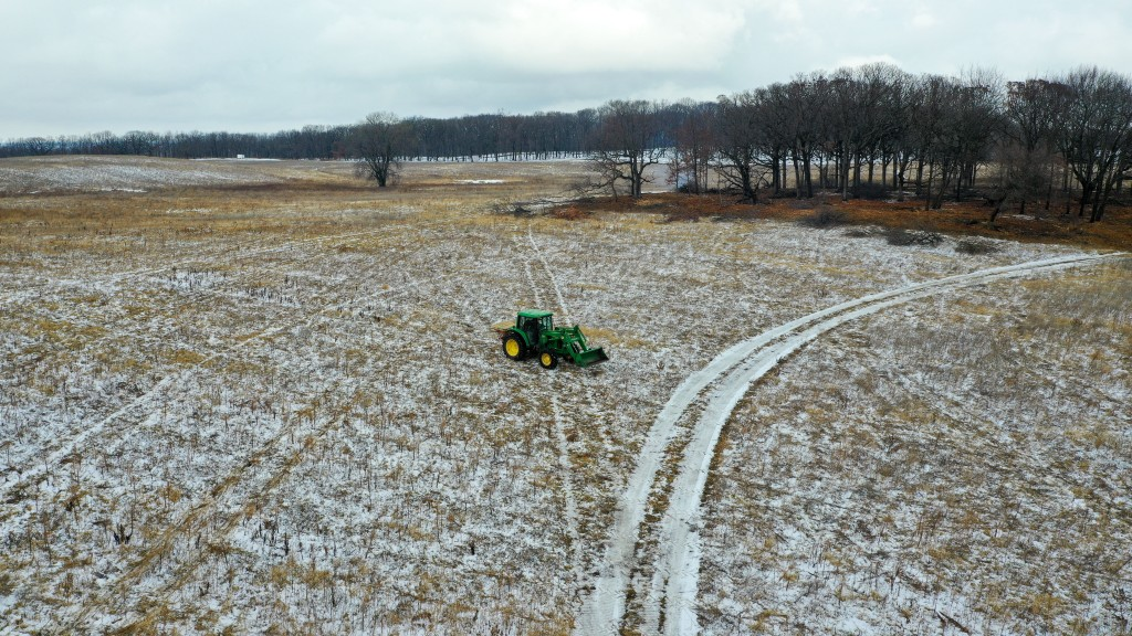 A tractor spreads native seed in a former farm field. Photo © Mike Borkowski.