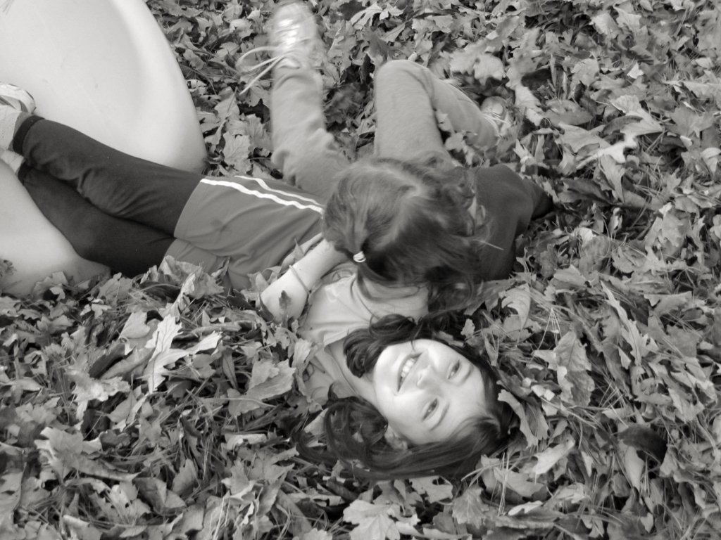 The author's daughters playing in a backyard leaf pile. Photo © Eileen Davis.